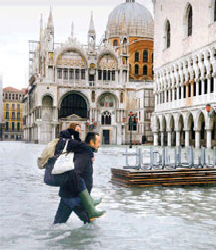 Woman is helped across Venice's St Mark's Square