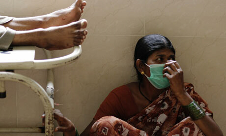 Surrounded by corpses of swine flu victims, woman wears a mask as preventive measure