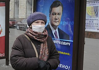 Woman wears a face mask at a bus stop in Kiev, Ukraine