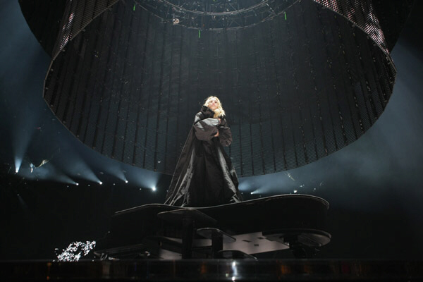 Madonna, the Gothic goddess, stands upon a black piano soon to be surrounded by images of cascading water ... water that eventually changes to white lava !