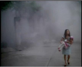 Young woman holding infant walks from cloud of dust